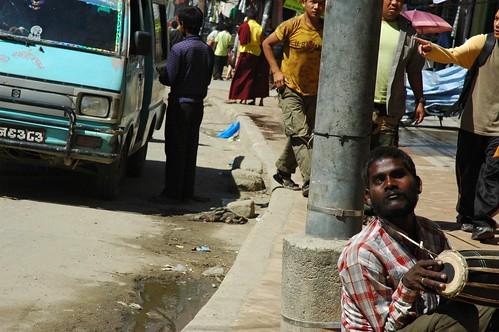 Blind street musician with tabla drum, street beggar, turquoise van taxi, Tibetan monks, taxi drivers and riders, entrance to Bodhanath (Bodha), Kathmandu, Nepal by Wonderlane