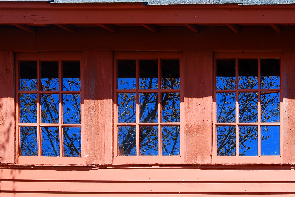 Blue sky and a tree reflected in three windows, with red siding.