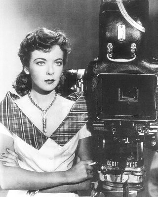 A black and white photo of Lupino. She stands with her arms crossed, looking determined and holding a cigarette next to a large camera that takes up as much of the photo as she does.