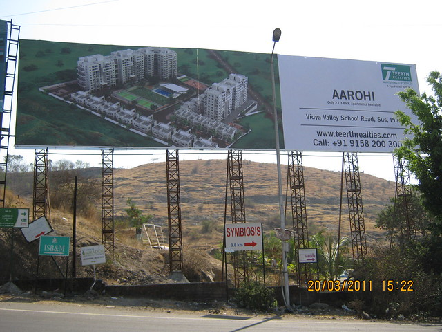 Hoarding of Teerth Realties' Aarohi, 2 BHK & 3 BHK Flats near Vidya Valley School at Sus Pune at Sus - at Pashan Sus Road Mumbai Bangalore Bypass Junction