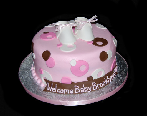 pink white and brown sassy circles baby shower cake with booties