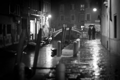 Venetian Noir, Venice (flatworldsedge) Tags: city bridge venice bw white black film water rain night umbrella canal couple noir candid grain bn softfocus af canon50mmf18 fin venezia yahoo:yourpictures=blackandwhite yahoo:yourpictures=love yahoo:yourpictures=happiness