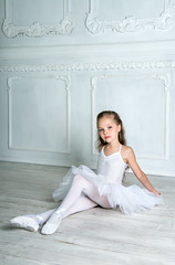 A little adorable young ballerina in a playful mood in the interior studio posing on camera (tigercop2k3) Tags: school light people ballet white cute art girl beautiful beauty smile childhood kids female pose studio happy person dance costume kid model education ballerina pretty artist child dress dancing emotion little expression feminine background traditional small joy innocent young adorable posing happiness dancer grace learning balance performer pleasure tender tutu elegance caucasian balletslippers pointeshoes russianfederation