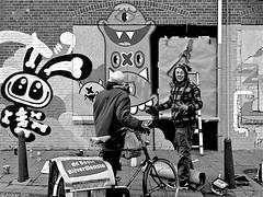 Conversation about art (Akbar Simonse) Tags: street people bw streetart holland blancoynegro netherlands monochrome amsterdam bicycle graffiti zwartwit candid nederland streetphotography denhaag bn thehague fiets lastplak schilderswijk dscn0438 agga straatfotografie akbarsimonse krantenbezorger doodkonijn debestebijverdienste artisyatwork
