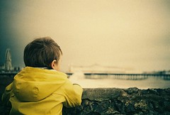 sea gazer (fotobes) Tags: winter boy sea portrait yellow wall pier lca xpro crossprocessed brighton dof felix head crossprocess grain depthoffield ear ferriswheel hood analogue raincoat groyne vignette brightonpier palacepier souwester kodatektachrome160t brightonwheel