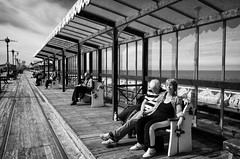 Relaxing On The Pier (nigelhunter) Tags: street light people urban woman sun man bench pier wooden couple track sleep candid seat relaxing bathe shelter doze blackpool