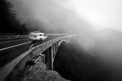 Into the Fog (Kevin Dinkel) Tags: road above bridge winter light sky bw white motion black blur mountains cold monochrome fog truck dark landscape photography drive high highway shadows darkness angle cloudy dusk faith wide over foggy pass windy yang trust determined yin ultrawide abyss disappear kevindinkel
