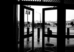 Exiting mall back to rainy winter (Robert S. Photography) Tags: street door winter bw ny reflection wet buses monochrome rain brooklyn canon mall outside view pavement powershot february posts flatbushave 2016 kingsplaza