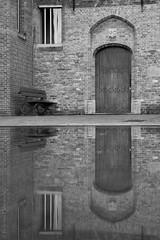 The couch and the door (rvanhegelsom) Tags: street door old city windows urban blackandwhite reflection building window water monochrome architecture buildings bench cityscape belgium outdoor brugge streetphotography historic historical bruges