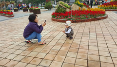 Getting down to it (Roving I) Tags: flowers boys children photography posing mothers vietnam tet lunarnewyear danang squatting