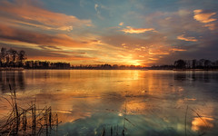 Strike of light 3 (piotrekfil) Tags: winter sunset sky sun sunlight lake ice nature water clouds reflections landscape pentax poland waterscape piotrfil