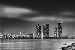 A Minute of Present Tense (skumar0108) Tags: city longexposure bridge blackandwhite bw reflection tower night clouds buildings lights freedom nightlights pentax florida miami path fineart citylights breeze cloudscape minute stratocumulus freedomtower