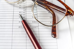 A Pen And Eyeglasses On a Page With Financial Data. (AudioClassic) Tags: pen paper bill education business document mathematics balance tax savings eyeglasses investment currency stockexchange banking wealth finance efficiency calculating scrutiny forecasting analyzing bankaccount bankstatement homefinances stockmarketdata