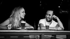 A beer and a chat (MyEyeSoul) Tags: newtown beer bw smile portrait candid street bar sydney together woman lady saturday relaxing man happyjack tattoo australia chill chilling posers story chat chatting pub kingst laughing