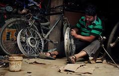 Bicycle Man ( Jamie Mitchell) Tags: travel nepal portrait people man male feet bicycle work hands asia wheels culture dirty kathmandu nepalese tradition dust trade patan mechanic nepali