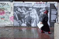 Homeless Roma passes in front of pro-refugee billboard. Brussels, March 2016. (joelschalit) Tags: brussels streetart roma belgium refugee iraq homeless middleeast diversity bruxelles syria gypsy rom immigration immigrant ethnicity migrant belge multiculturalism asylumseeker rueanspach