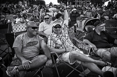 Peace! (Anne Worner) Tags: street sunset people blackandwhite bw man men monochrome hat sunglasses smiling shirt outside outdoors mono evening lowlight sitting legs chairs sandals candid crowd grain streetphotography wideangle georgetown sneakers plaid peacesign ricohgr crossed lawnchairs inthestreet beerdrinking niksilverefex anneworner 2016poppyfestival
