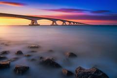 Endless (albert dros) Tags: sunset seascape netherlands dutch sunrise rocks seascapes bridges zeeland endless zeelandbrug albertdros