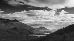 a marriage of sea and land (lunaryuna) Tags: sea sky bw panorama mountains monochrome beauty weather norway landscape islands bay blackwhite horizon hills shelter lunaryuna cloudscape settlement atmosphericperspective lofotenislands lightmood protectedbay