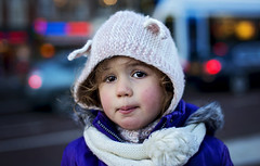 Sad face (Wojtek Piatek) Tags: street city winter portrait holland netherlands girl hat amsterdam scarf 50mm lights eyes child sad bokeh tram sigma portret fifty nifty dziecko oczy somy a99