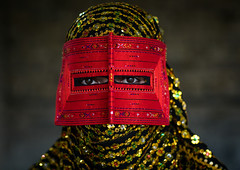 a bandari woman wearing a traditional mask called the burqa, Hormozgan, Minab, Iran (Eric Lafforgue) Tags: red portrait people woman beauty horizontal golden persian clothing eyes asia veil mask iran muslim islam religion hijab culture persia headshot hidden indoors covered iranian adultsonly oneperson traditionaldress burqa customs middleeastern frontview sunni burka chador 20sadult youngadultwoman balouch hormozgan onewomanonly lookingatcamera burqua  bandari  embroidering 1people  iro thursdaymarket  minab colourpicture  borqe panjshambebazar boregheh irandsc06762