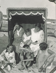 Family squints at the sun while at the beach (simpleinsomnia) Tags: old family boy white black beach girl monochrome vintage germany found blackwhite sand chair bright little antique snapshot sunny photograph littlegirl vernacular littleboy strandkorb foundphotograph squinting beachchair