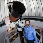 Dr. Oberst smiling as he poses with the college's telescope.