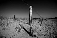 Keep away from the light (Simon Taylor Local Photographic) Tags: sky bw lighthouse holland netherlands fence wire sand post footprints barbed