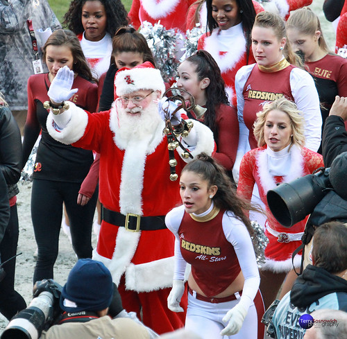 Santa is surrounded by cheerleaders and dancers.