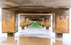 Underside of Hanalei Pier long exposure (ManassasWarrentonCameraClub) Tags: ocean longexposure travel sea usa blur tourism beach concrete island hawaii sand waves jetty perspective blurred nobody calm structure underside kauai receding hanaleipier destination unusual underneath hanaleibay