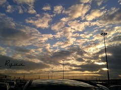 gorgeous clouds (Ryuu) Tags: blue sunset sky urban orange cloud sunlight reflection cars yellow skyline clouds composition skyscape gold lights reflecting golden evening heaven sundown dusk silhouettes surface sunrays parkingspace settingsun lampposts peakingsun