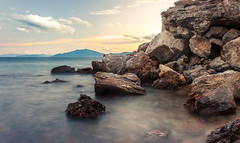 Rocks + Sunset (Nick Panagou) Tags: longexposure light sunset sea sky seascape mountains colour beach water rock clouds contrast landscape rocks warm colours greece skyandclouds sunsetlight cloudysky waterscape contrasted greatphotographers thessaly flickrsbest bestshotoftheday magnesia canon400d flickrbest bestphotographer canonefs1855mmf3556isii