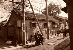 "China Beijing hutong backalley with scooters and old-looking houses - ""Hutong Style"" (moreska) Tags: china travel blackandwhite tourism rooftop monochrome bicycle sepia architecture cycling asia afternoon backalley outdoor capital beijing structures kingdom scooter oldschool retro nostalgia motorbike wires alleyway 1950s transportation hutong middle narrow"