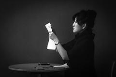 Paperwork (John St John Photography) Tags: newyorkcity blackandwhite bw woman newyork pen paper table pad streetphotography indoor smartphone seated 7thavenue tibetanart rubinmuseum 17thstreet candidphotography himalayanart peperwork