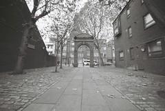 Thrawl Street (goodfella2459) Tags: street white black london film analog 35mm nikon plus whitechapel milf ilford fp4 f4 125 thrawl