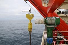 Ein Kolbenkernprobenehmer (piston corer) hängt am Seil neben der Bordwand. Gleich wird er in 1300 mm Tiefe hinabgelassen, um viele Meter in das weiche Sediment auf dem Meeresboden einzudringen und einen entsprechend langen Sedimentkern zu entnehmen.