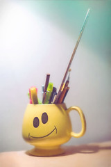 Happiness is (ScottNorrisPhoto) Tags: yellow pen pencil ceramic happy photography coffeecup happiness brush explore marker write draw ruler bigsmile tabletop warmtones goofygrin pastelcolors dramaticlight stilllifephotography portraitorientation 365project scottnorrisphotography