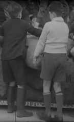 Boys with sacks of spuds (theirhistory) Tags: uk england history boys shirt kids children internet lorry jacket jumper shorts sack wellies rubberboots lifting newsreel