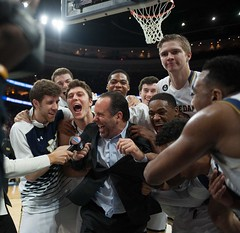 For the third time in eight days, the Irish men pulled off a late, dramatic win in the NCAA tournament. Players mob head coach Mike Brey after the 61-56 win over Wisconsin, which advanced Notre Dame to the Elite Eight for the second straight year. Photo c