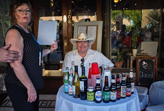 Name Your Poison (Anne Worner) Tags: street door woman plants man window beer smiling sign shirt reflections menu table real outside lights restaurant closed texas looking sundown wine bottles display candid streetphotography wideangle georgetown sidewalk cups pottedplants drinks booze inside nightlife unposed cowboyhat brass ricohgr carafe stetson stopped redcups pellegrino plasticcups hatband nameyourpoison haveadrink goodoleboy 183mm anneworner poppyfestival2016