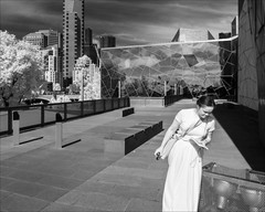 melbourne-1634-ps-w (pw-pix) Tags: trees sky urban blackandwhite bw woman glass stone clouds fence walking ir lights warm shadows steel patterns floating sunny australia federationsquare melbourne cage victoria seats paving infrared barrier cbd poles hovering zinc enclosure bollards paved buidings fedsquare edgeauditorium