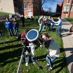 Students looking through telescopes.