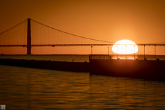Elliptical Sun 037A1739 (lycheng99) Tags: sf sanfrancisco california bridge sunset sky sun silhouette reflections golden bay gg glow pacific bridges pacificocean goldengatebridge goldengate sanfranciscobayarea ggbridge sfbayarea touchdown suspensionbridge pacificcoast goldensky