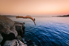 Diving after sunset (frfourrier) Tags: blue sunset sea sky cliff woman colour girl sport canon colours action stones diving athens greece