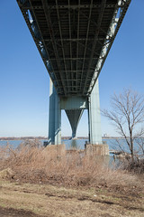 Beneath the Verrazano-Narrows Bridge (Erin Cadigan Photography) Tags: auto road city nyc newyorkcity bridge newyork tower vertical architecture brooklyn river outdoors bay harbor daylight traffic suspension steel under perspective bluesky cable double structure deck transportation transit toll underside vehicle mta borough daytime below hudson underneath statenisland beneath span narrows roadway verrazano verrazanonarrows fortwadsworth