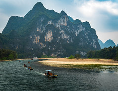 River traffic.jpg (Photos4Health) Tags: china old morning travel sunset shadow mountain man male guy nature water ecology silhouette sunrise river dark person li boat reflex clothing fisherman ancient scenery asia village place guilin yangshuo famous hill chinese scenic bamboo elderly fisher sail stick tradition guizhou karst villager guangxi ecotourism xingping