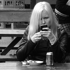 What's App? (Akbar Simonse) Tags: street people urban bw holland blancoynegro netherlands girl monochrome square phone zwartwit candid nederland streetphotography denhaag bn smartphone blond mobilephone cocacola thehague leatherjacket mobieltje vierkant agga straatfotografie img1053 akbarsimonse