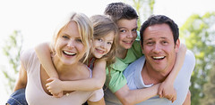 Couple giving two young children piggyback rides smiling (byzzarro) Tags: familia mama papa compaia hijos