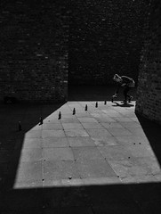 collecting (Georgie Pauwels) Tags: light blackandwhite sun girl monochrome shadows bottles candid olympus row line moment collecting streetpgotography