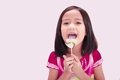 Beautiful little girl with lollipop (diary of moon) Tags: pink portrait people food white color cute girl beautiful beauty smile face childhood female studio asian fun happy person one kid funny colorful pretty child hand looking candy little sweet eating circus expression background joy young adorable lifestyle happiness sugar human cheerful lollipop